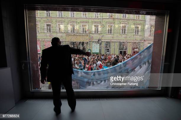 Argentinian football fans are told to remove their banner from across the window of the Moscow Audi dealership as they enjoy the World Cup party...