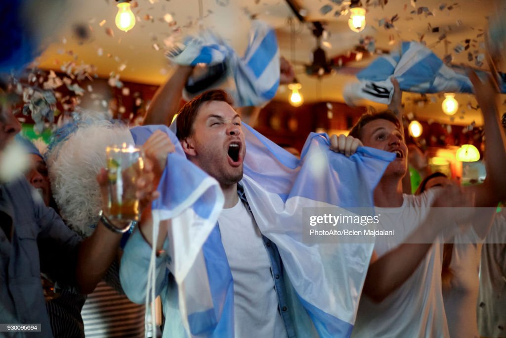 Argentinian football fans celebrating victory in bar : Stock Photo