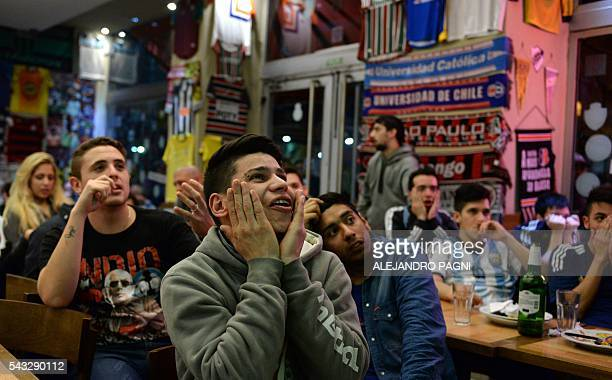 Argentinian football fans react in a Buenos Aires' downtown bar after Argentina's national team was defeated by penalty kicks against Chile during...
