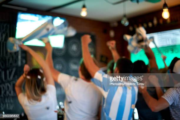 Argentinian football fans watching football match at sports bar