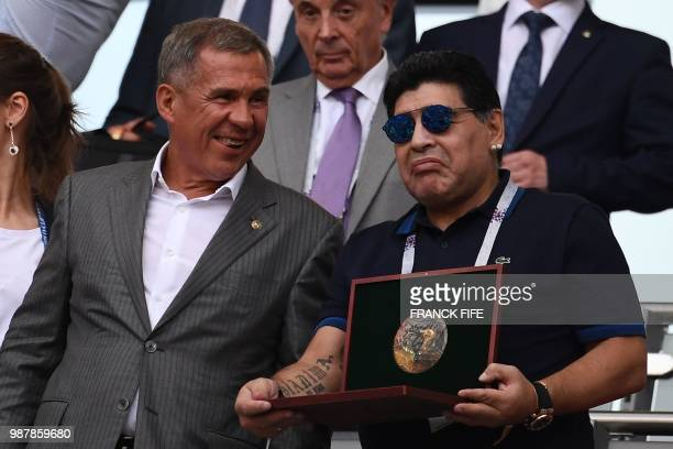 Argentinian football legend Diego Maradona poses with an award before the Russia 2018 World Cup round of 16 football match between France and...