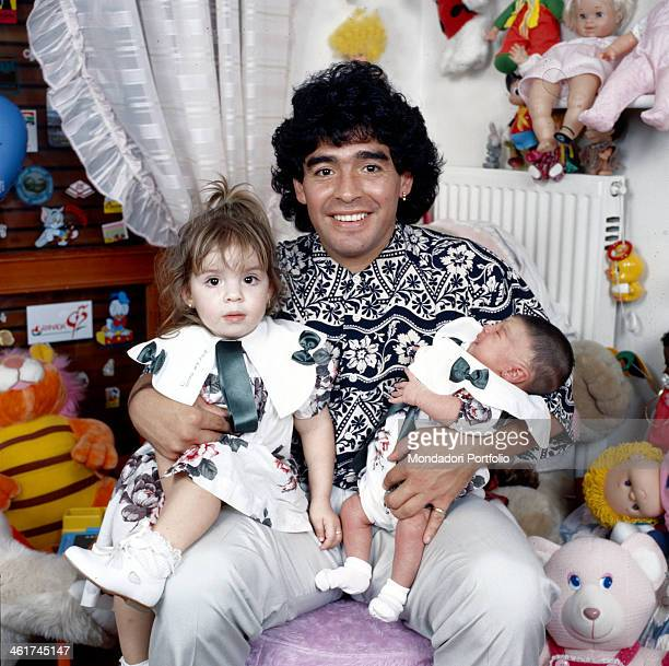 Argentinian football player Diego Armando Maradona sitting in a small bedroom with his daughters Dalma e Giannina in his arms Italy 1989
