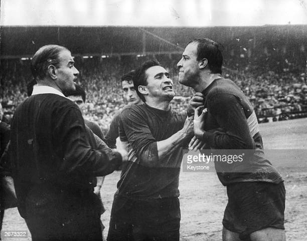 Argentinian footballer Silveiro captain of Boca tries to prevent his teammate Alfredo Rojas from attacking the referee who has just sent him off...