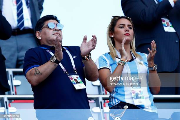 Argentinian former football player Diego Armando Maradona and his girlfriend Rocio Oliva applaud from the grandstands during the Russia 2018 World...