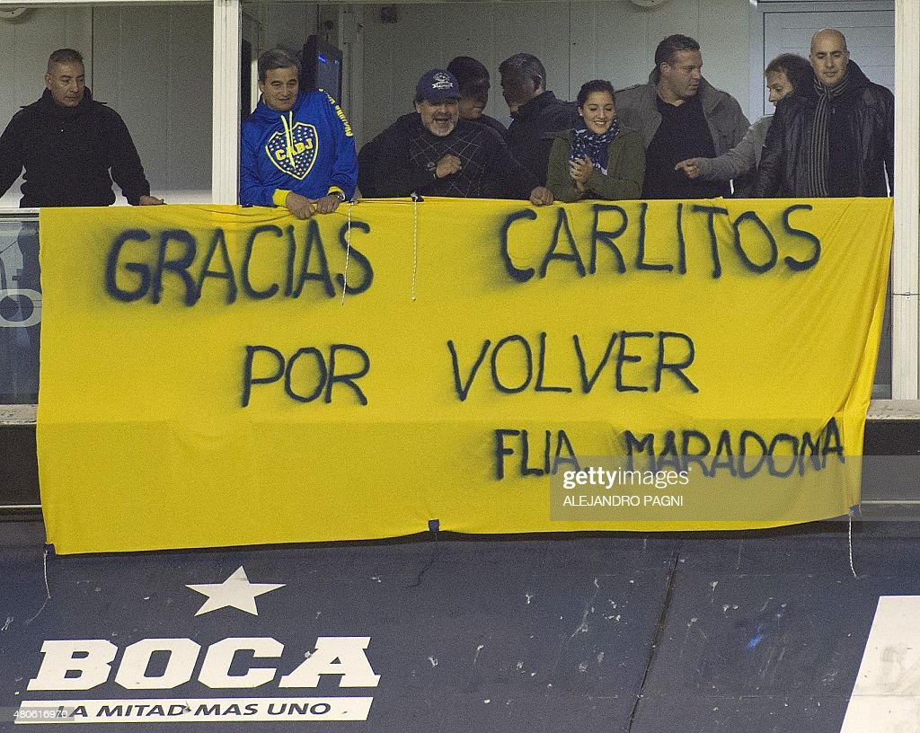 Argentinian former footballer Diego Maradona (C) cheers for Boca Juniors' newly returned player Carlos Tevez during his official presentation at La Bombonera stadium in Buenos Aires,on July 13, 2015. The banner reads 'Thank you Carlitos for coming back. The Maradona family'.