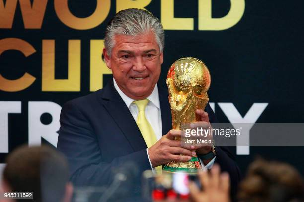 Argentinian former soccer player Hector Miguel Zelada holds the FIFA Trophy during the FIFA Trophy Tour at Residencia Oficial de Los Pinos on April...