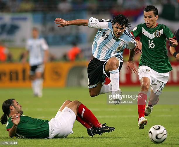 Argentinian forward Carlos Tevez jumps to avoid tackle by Mexican defender Rafael Marquez next to Mexican defender Mario Mendez during the World Cup...