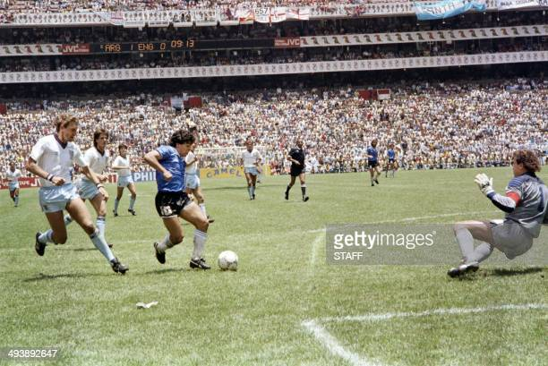 Argentinian forward Diego Armando Maradona runs past English defender Terry Butcher on his way to dribbling goalkeeper Peter Shilton and scoring his...