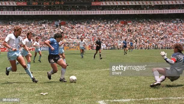 Argentinian forward Diego Armando Maradona runs past English defender Terry Butcher on his way to dribbling goalkeeper Peter Shilton and scoring his...