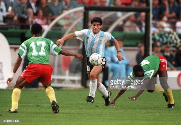 Argentinian forward Diego Maradona juggles with the ball as he runs past Cameroon's Benjamin Massing during the World Cup opening soccer match...