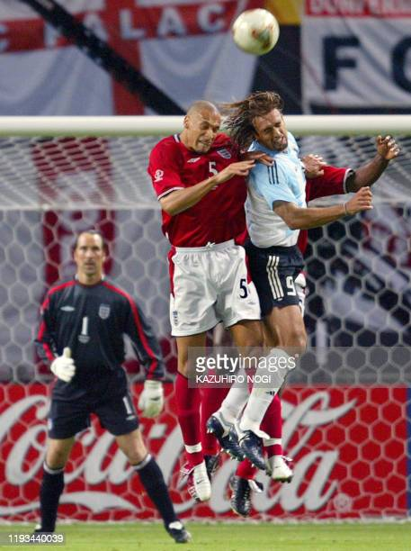 Argentinian forward Gabriel Batistuta and English defender Rio Ferdinand collide as they head the ball during the Group F first round match...
