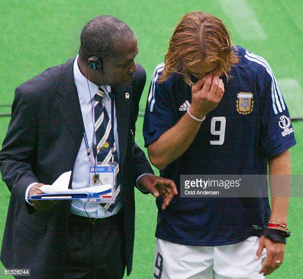 Argentinian forward Gabriel Batistuta is comforted by a FIFA official as he leaves the pitch after the Group F first round last match...