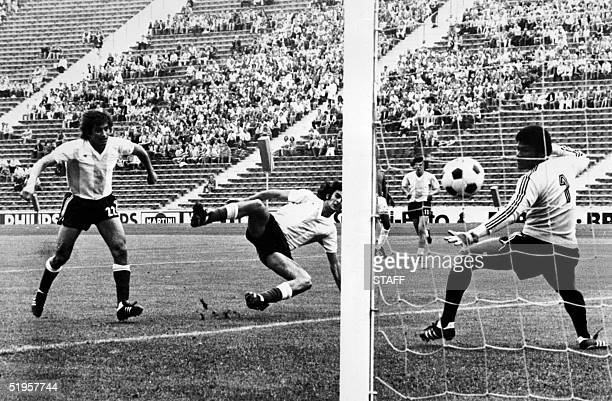 Argentinian forward Hector Yazalde scores a goal past Haitian goalkeeper Henry Francillon as forward Mario Kempes falls down during the World Cup...