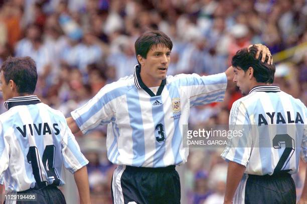 Argentinian forward Jose Chamot congratulates his teammates Roberto Ayala and Nelson Vivas 14 June at Toulouse Stadium after the 1998 Soccer World...