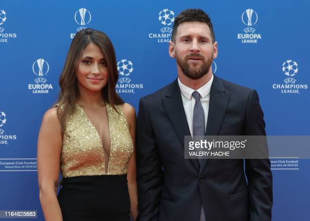 Argentinian forward Lionel Messi and his wife Antonella Roccuzzo Messi pose as they arrive prior to the UEFA Champions League football group stage...