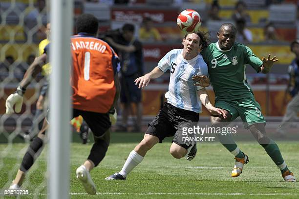 Argentinian forward Lionel Messi and Nigerian forward Victor Obinna fight for the ball in front of Nigerian goalkeeper Ambruse Vanzekin during the...