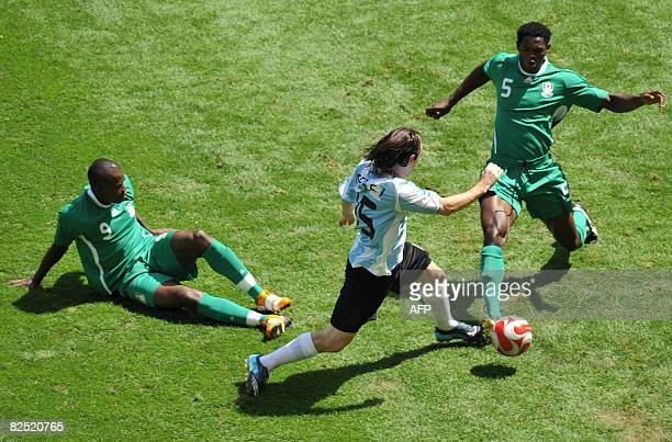 Argentinian forward Lionel Messi fights for the ball with Nigerian defender Dele Adeleye next to Nigerian forward Victor Obinna during the men's...