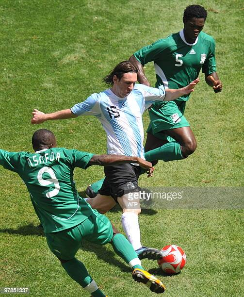 Argentinian forward Lionel Messi is challengeb by Nigerian forward Victor Obinna and defender Dele Adeleye during the men's Olympic football final...