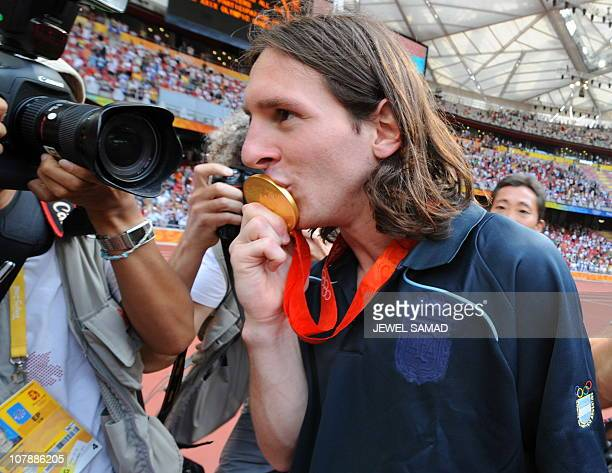 Argentinian forward Lionel Messi kisses his gold medal as he leaves the pitch after attending the men's Olympic football tournament medal ceremony at...