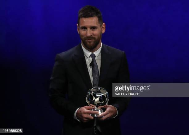 Argentinian forward Lionel Messi receives his trophy of UEFA Forward of the Year during the UEFA Champions League football group stage draw ceremony...