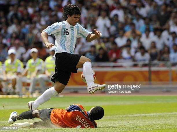 Argentinian forward Sergio Aguero jumps with the ball over Nigerian goalkeeper Ambruse Vanzekin during the men's Olympic football final Argentina vs...