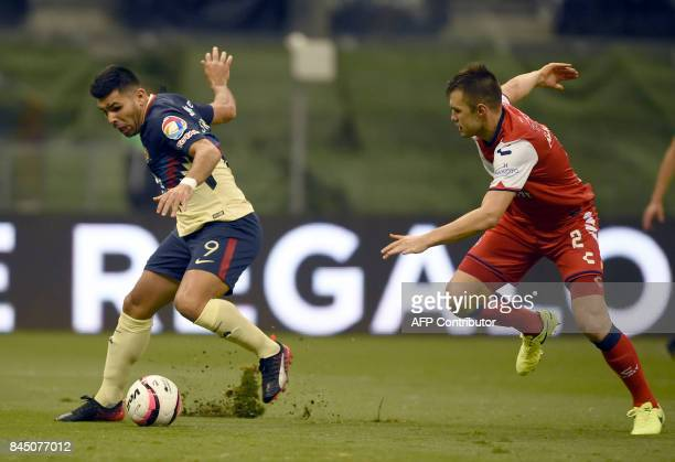 Argentinian forward Silvio Romero of America vies for the ball with defender of Veracruz Omar Alvarez during their Mexican Apertura tournament...