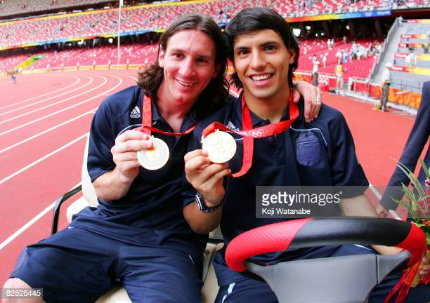 Argentinian forwards Lionel Messi and Sergio Aguero gold medal pose during the men's Olympic football tournament medal ceremony at the national...