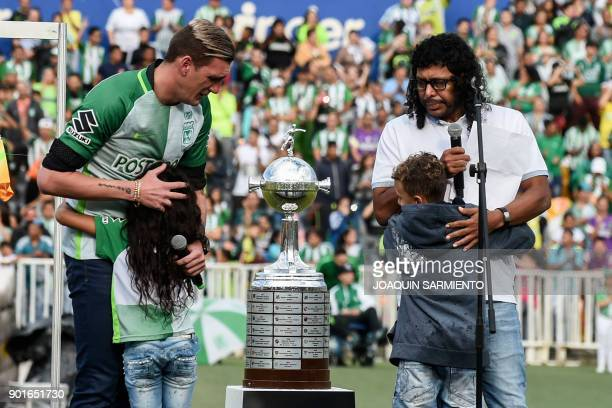 Argentinian goalkeeper Franco Armani and Colombian former goalkeeper Rene Higuita are hugged by children during Armani's farewell from Colombia's...