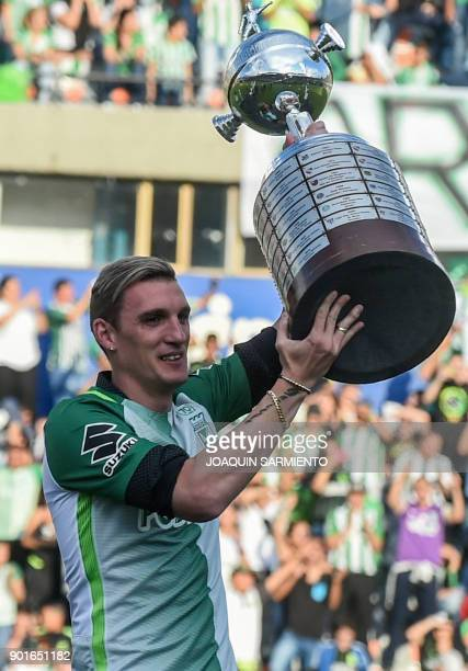 Argentinian goalkeeper Franco Armani rises the Libertadores 2016 trophy during Armani's farewell from Colombia's Atletico Nacional at the Atanasio...