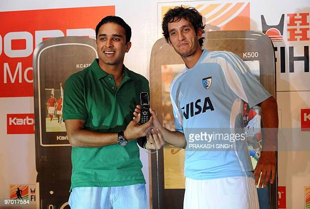 Argentinian hockey player Lucas Vila and India hockey player Deepak Thakur pose with a Karbonn mobile handset as the International Federation of...