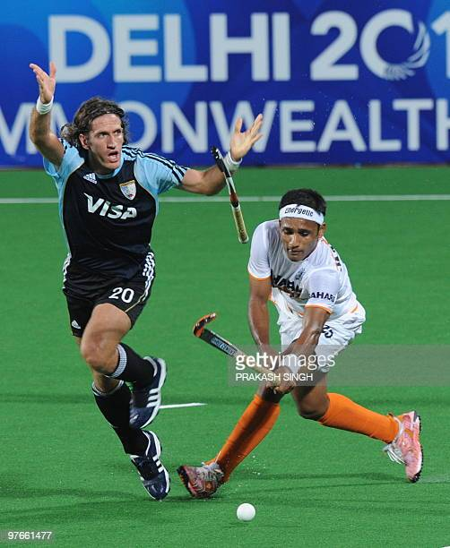 Argentinian hockey player Tomas Argento and Indian hockey player Dhananjay Mahadik vie for the ball during their World Cup 2010 clasification match...