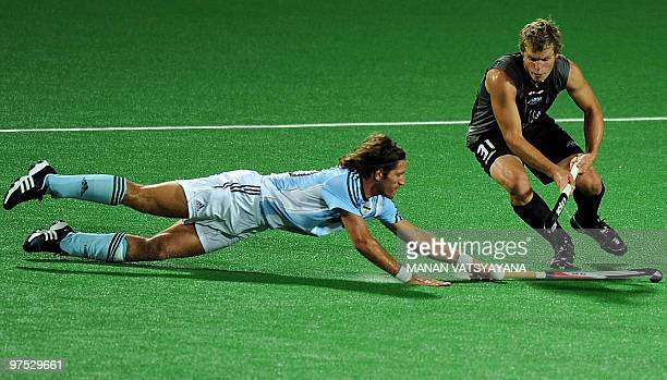 Argentinian hockey player Tomas Argento vies for the ball with New Zealand hockey player Steve Edwards during their World Cup 2010 match at the Major...