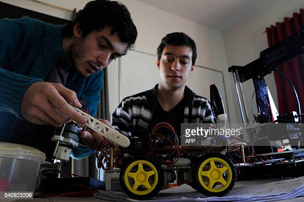 Argentinian industrial engeneering student of the National University of Cuyo Marcos Bruno shows a robot made by him next to his collaborator...
