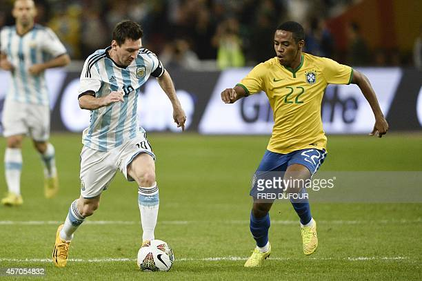 Argentinian Lionel Messi vies with Brazilian Elias during the Superclasico football match Brazil versus Argentina at the National stadium in Beijing...