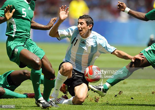 Argentinian midfielder Angel Di Maria is tackled by Nigerian forward Solomon Okoronkwo next to Nigerian defender Dele Adeleye during the men's...