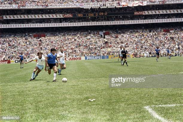 Argentinian midfielder Diego Maradona dribbles past two English defenders on June 22, 1986 in Mexico City during the World Cup quarterfinal soccer...