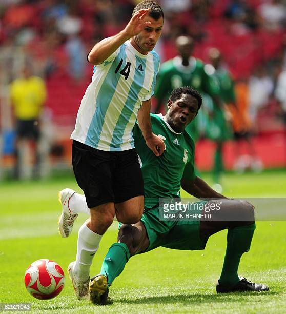 Argentinian midfielder Javier Mascherano is tackled by Nigerian defender Dele Adeleye during the men's Olympic football final Argentina vs Nigeria at...
