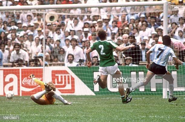 Argentinian midfielder Jorge Burruchaga beats West German goalkeeper Harald Schumacher to score the winning goal during the World Cup final between...