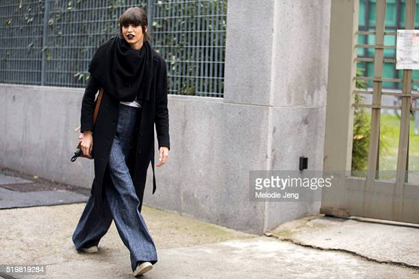 Argentinian model Mica Arganaraz wears a loose black scarf a black jack white top and blue pleated widelegged trousers after the Bottega Veneta show...