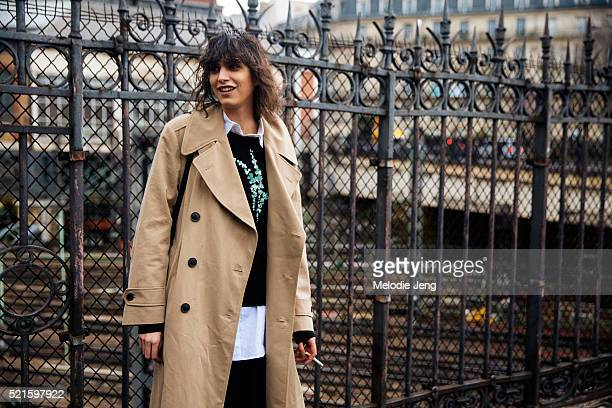 Argentinian model Mica Arganaraz weasr a tan trench coat and a Dries Van Noten embroidered top after the Dries Van Noten show on March 02 2016 in...