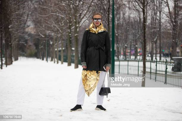 Argentinian model Moira Berntz wears reflectivie sunglasses a black trenchcoat gold reflective blanket and YSL purse after the Chanel show during...