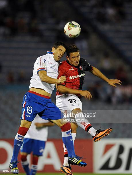 Argentinian Newell's Old Boys's Ezequiel Ponce vies for the ball with Uruguayan Nacional's Andres Scotti during their Libertadores Cup football match...