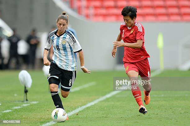 Argentinian player Mariana Larroquete and Chinese player Li Dongna vie for the ball during their Brasilia International Tournament football match at...