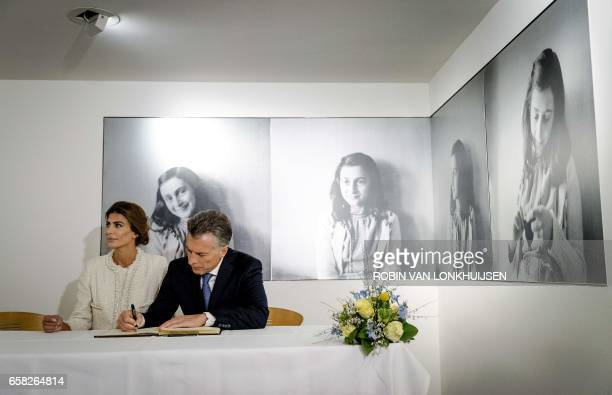 Argentinian president Mauricio Macri and his wife Juliana Awada sign the guest book at the Anne Frank House museum in Amsterdam on March 27 during...