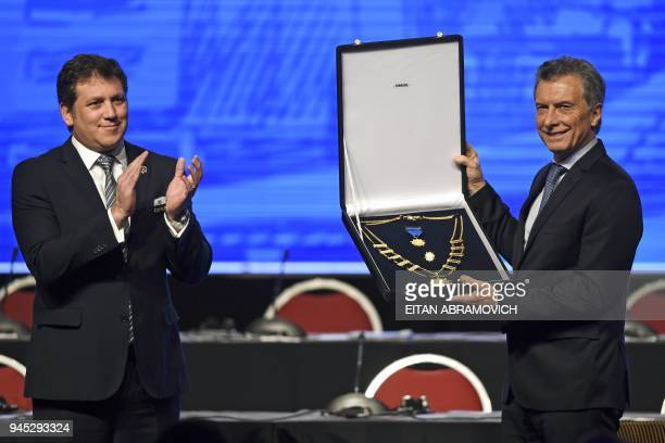 Argentinian President Mauricio Macri is condecorated by Conmebol President Alejandro Dominguez during the 68th Conmebol Council meeting in Buenos...