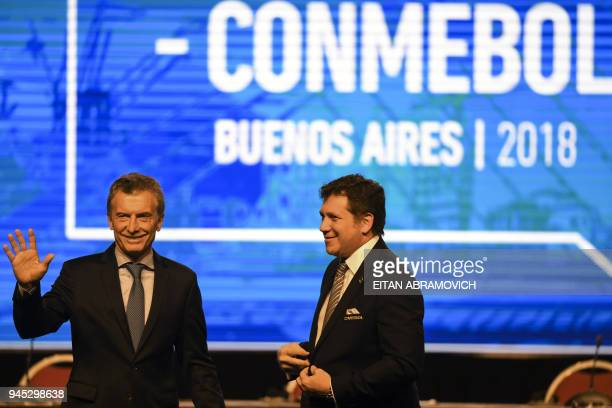 Argentinian President Mauricio Macri waves next to Conmebol President Alejandro Dominguez during the 68th Conmebol Council meeting in Buenos Aires...