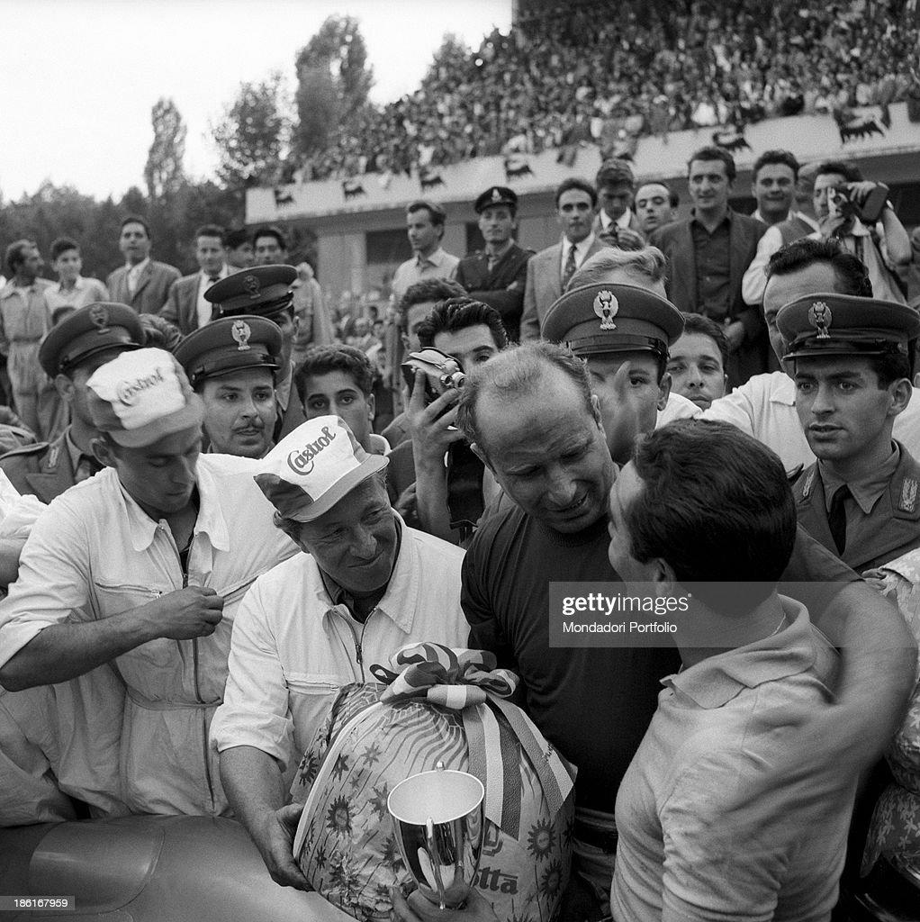 Juan Manuel Fangio hugging Eugenio Castellotti : News Photo