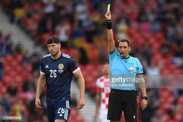 Argentinian referee Fernando Rapallini presents a yellow card to Scotland's defender Scott McKenna during the UEFA EURO 2020 Group D football match...