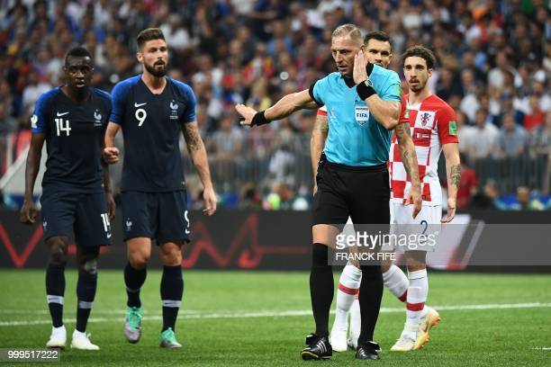 TOPSHOT Argentinian referee Nestor Pitana gestures as he listens to indications from the Video Assistant Refereeing during the Russia 2018 World Cup...