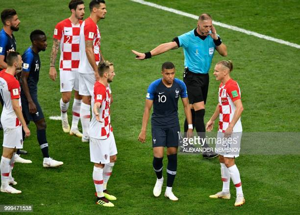 Argentinian referee Nestor Pitana speaks with video referees about a hand fault commited by Croatia's forward Ivan Perisic during the Russia 2018...